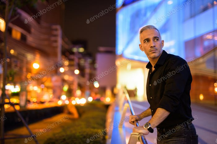 Portrait of attractive man at night on the streets thinking