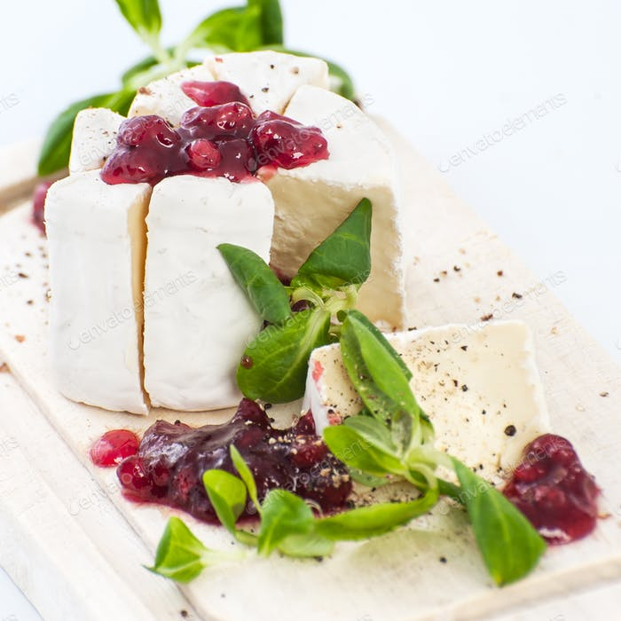 Cheese Brie with cowberry sauce and fresh lettuce leaves.
