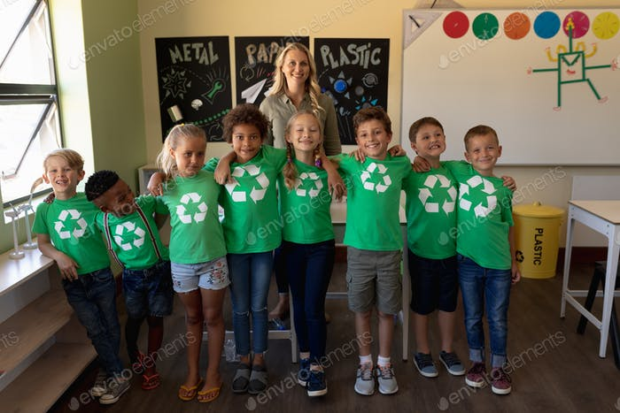 Female school teacher with a group of schoolchildren wearing green t shirts with a white recycling l