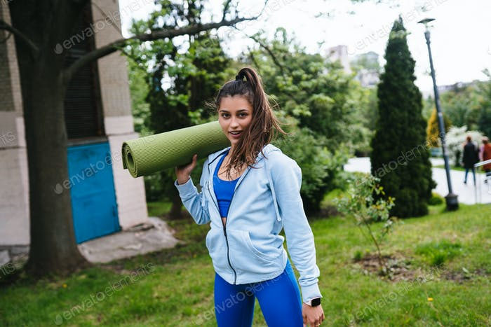 Young woman walking in urban park holding fitness rug