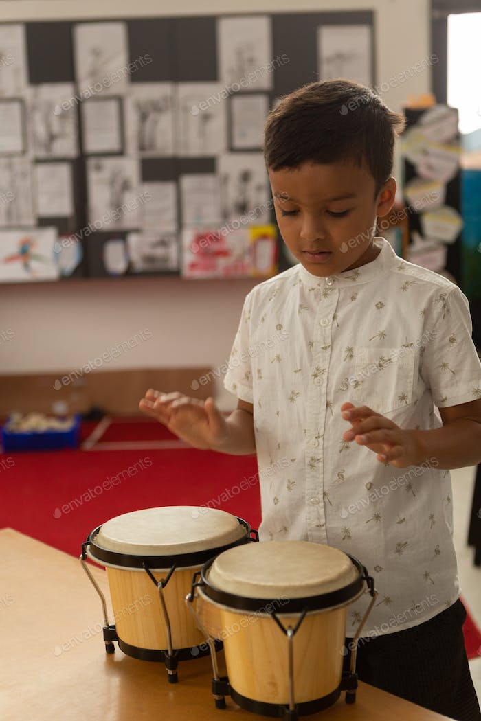 Front view of focused mixed-race schoolboy playing bongo in a classroom at elementary school