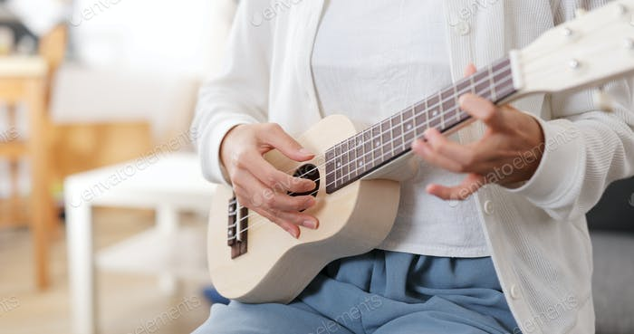 Woman play a song on ukulele at home