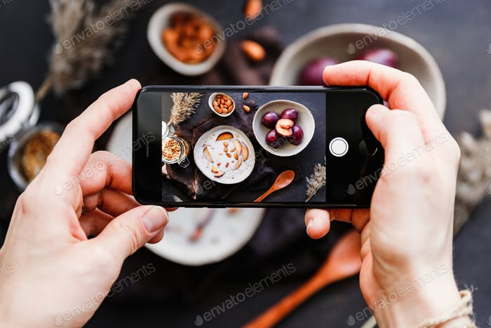 Hands hold smartphone and take picture of morning porridge with almond and sliced plum