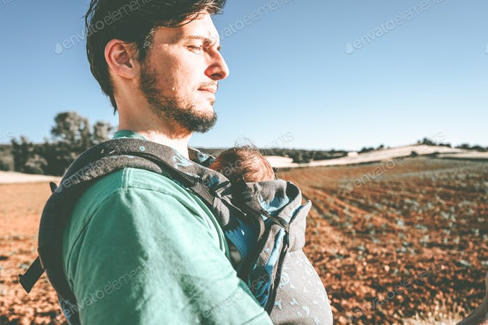 Single male parent carrying her baby with a backpack