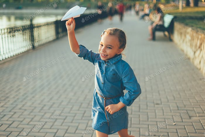 Girl playing, running with toy paper airplane