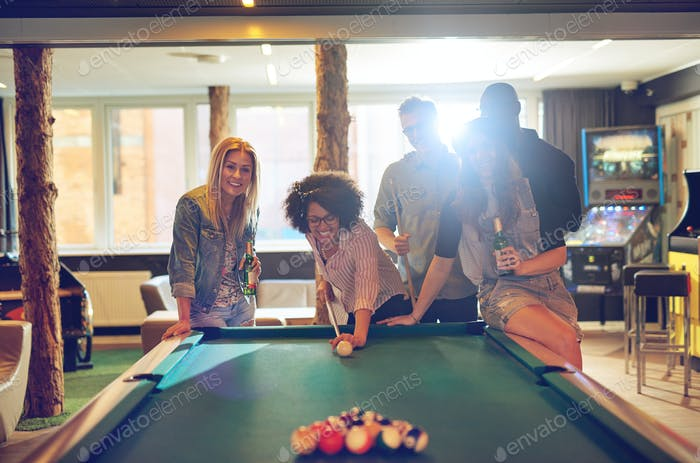 Friends in game room playing pool