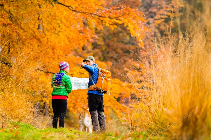 Couple hiking with map in autumn forest