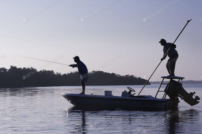 A silhouette of  a fly fisherman and a guide casting for redfish from a flats boat poling skiff in