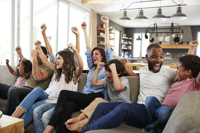 zwei familien beobachten sport auf fernseher und jubeln