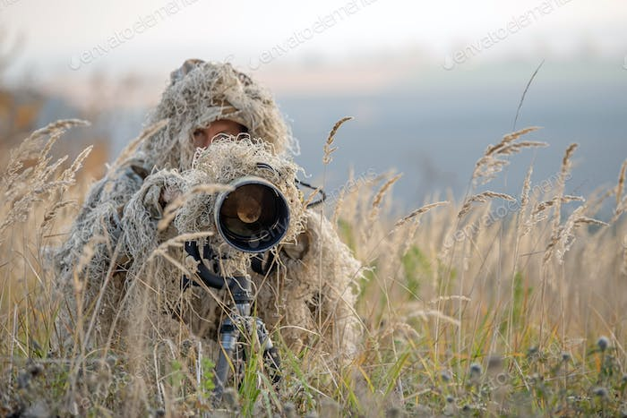 Wildlife photographer in the ghillie suit working