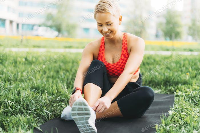 Attractive fit young woman in sport wear stretching on green grass in city park