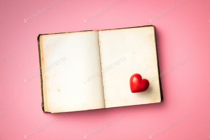 Liebeskonzept. Herz auf offener Vintage-Buch.