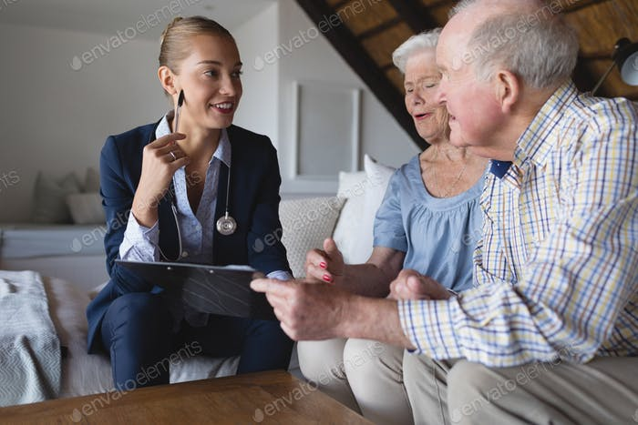 Female doctor and senior couple laughing and discussing over clipboard at home