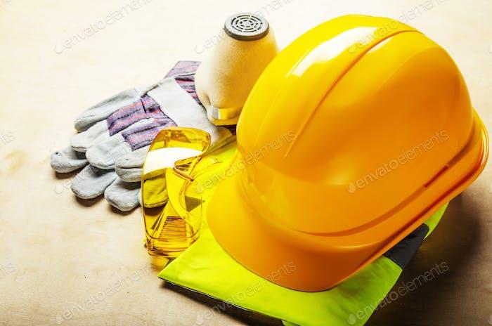 Gelbe Kunststoff-Harthut, Brille, Atemschutzmaske und Schutzhandschuhe auf Sperrholz