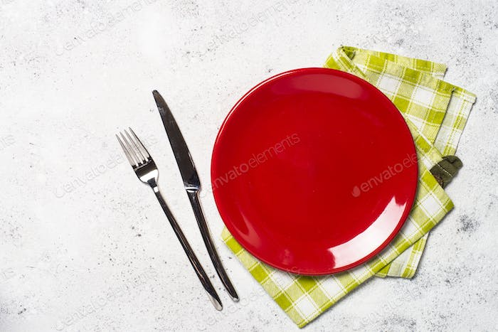 Red plate, cutlery and tablecloth on light stone table.