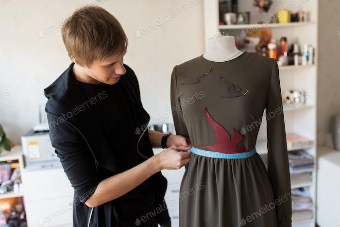 Modedesigner mit Schnuller machen Kleid im Studio
