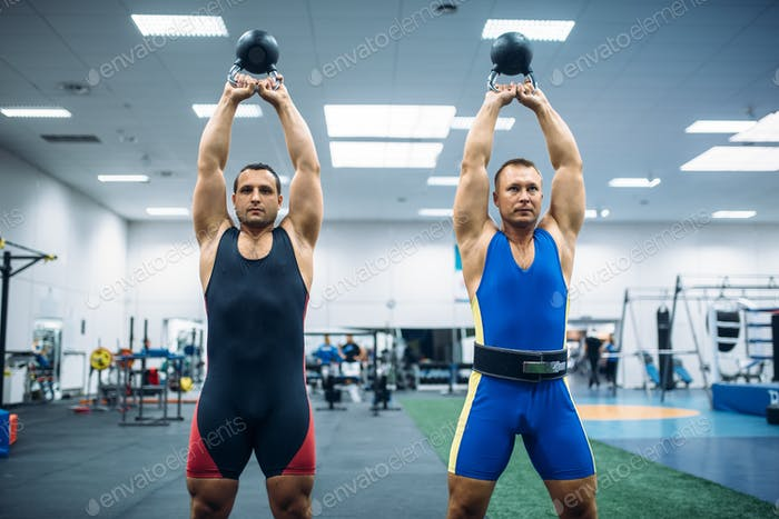 Male lifters lifted kettlebells over thier heads