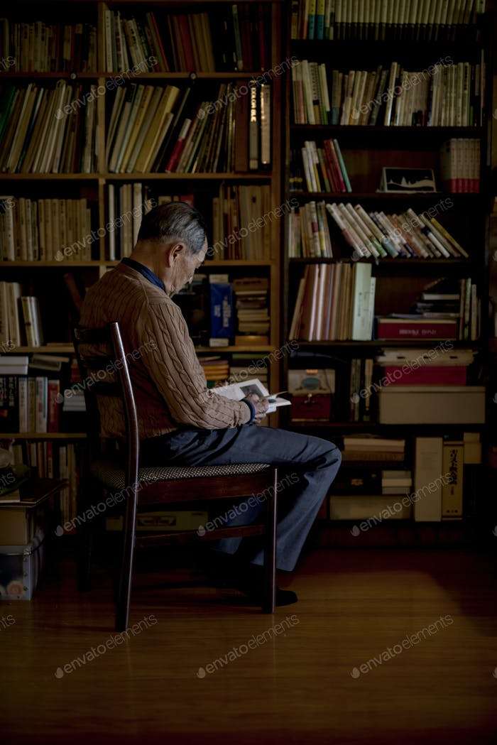 Elderly man sitting on chair in front of bookcase, reading book.