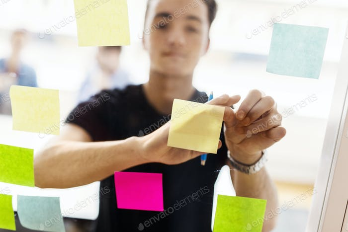 Young man looking at adhesive notes