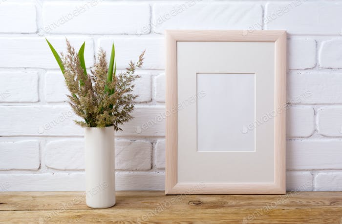 Wooden frame mockup with grass and green leaves in cylinder vase