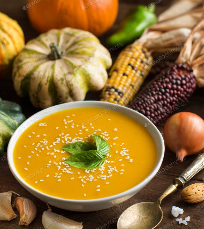 Fresh pumpkin soup with a spoon and vegetables