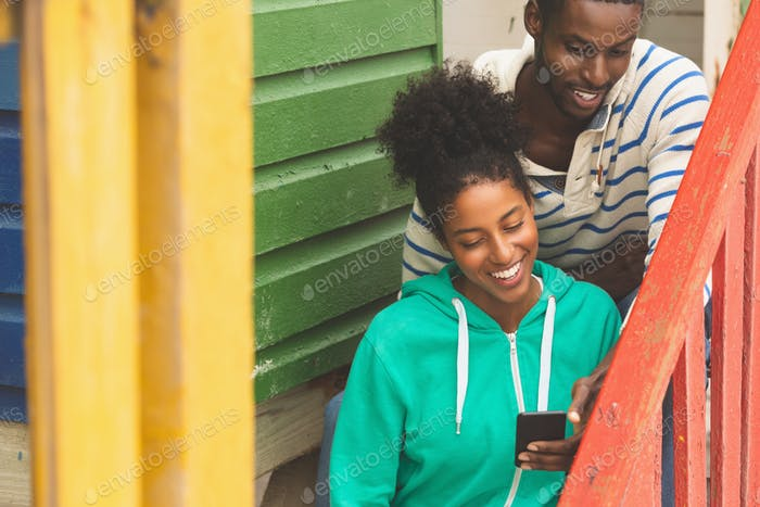 Front view of happy Multi-ethnic couple using mobile phone while sitting near beach hut