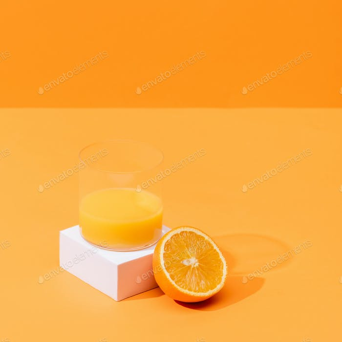 fresh orange juice in glass near half of orange and white cube isolated on orange