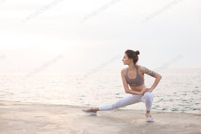 Thoughtful girl in sporty top and leggings practicing yoga with