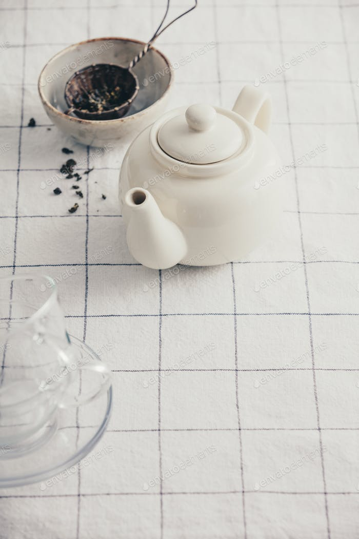 White teapot on the checkered table cloth