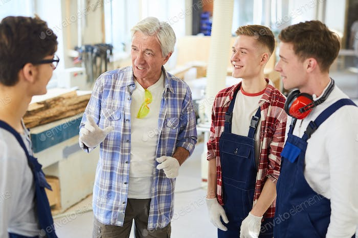 Confident carpenter gesturing hands while sharing experience with interns
