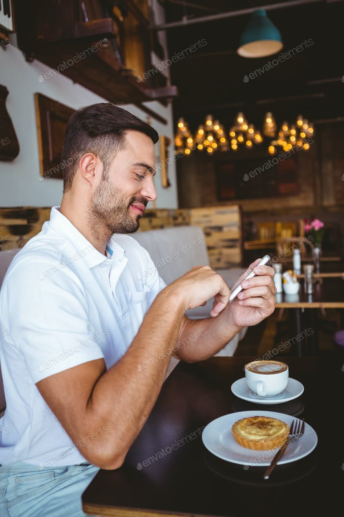 Side view of young man having cup of coffee and pastry while texting in a cafe