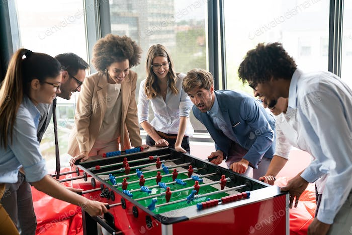 Employees playing table soccer indoor game in the office during break time