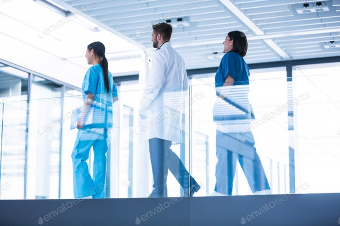 Doctor with nurses walking in corridor