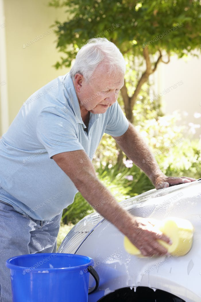 Senior Man Washing Car In Drive