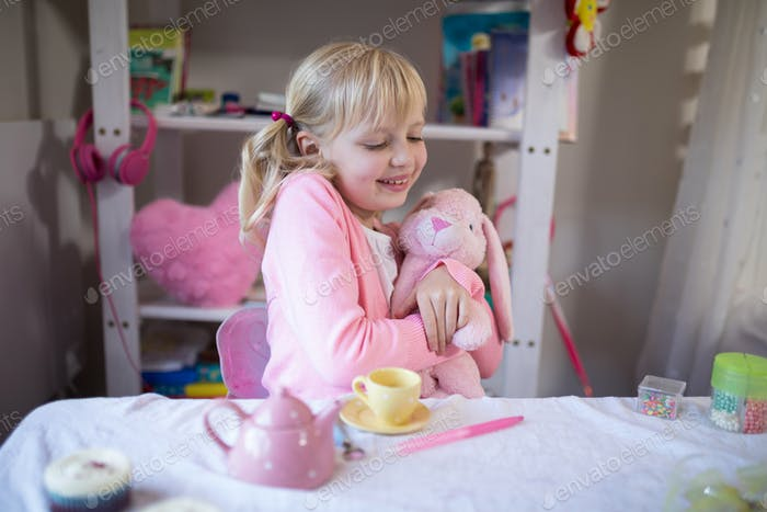 Smiling girl playing with a teddy bear and toy kitchen set
