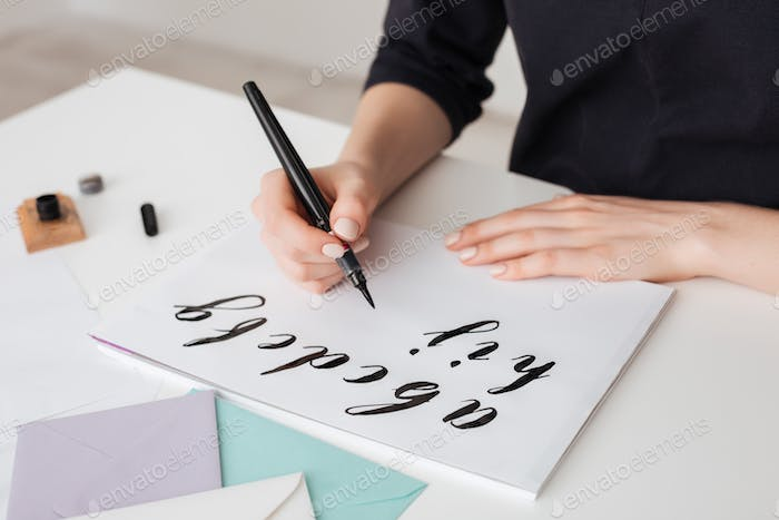Portrait of young woman hands writing alphabet on paper on desk  isolated