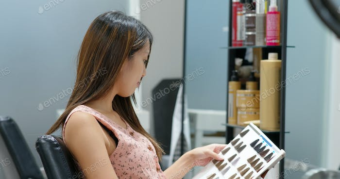 Woman look at color book of hair dye color at beauty salon
