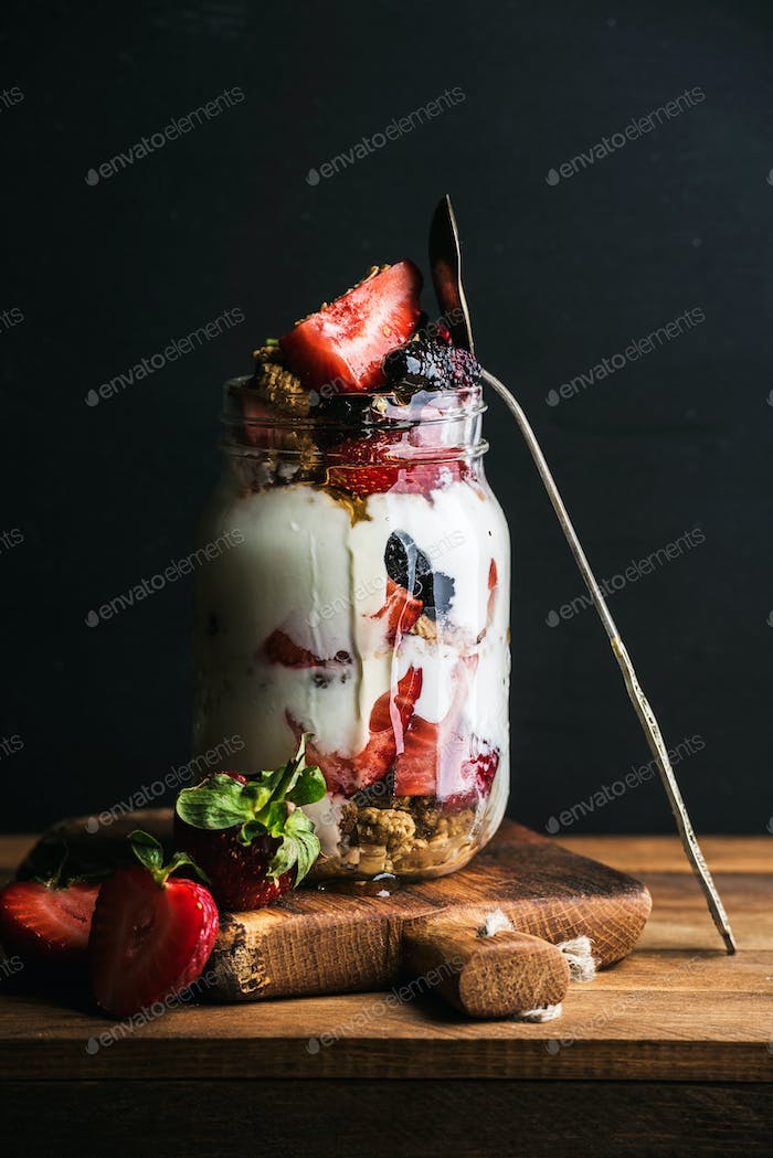 Yogurt oat granola with strawberries, mulberries, honey and mint leaves