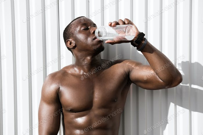 Portrait of a young thirsty african sportsman drinking water
