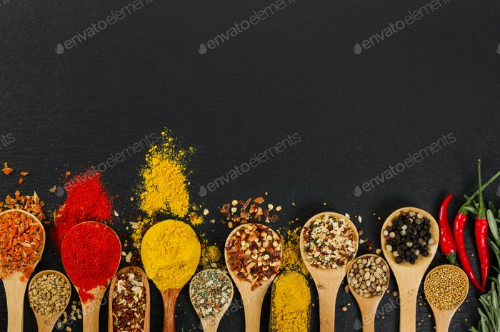 Various spices in wooden spoons on black slate background.