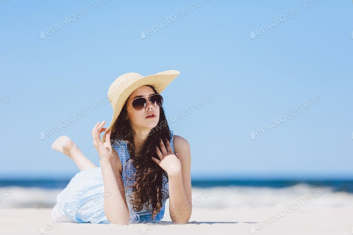 Young girl laying on the beach in a hat and sunglasses