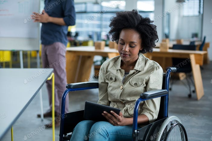 Disabled business executive in wheelchair using digital tablet