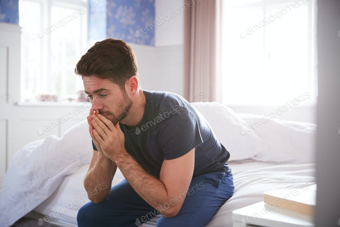 Man Wearing Pajamas Suffering With Depression Sitting On Bed At Home