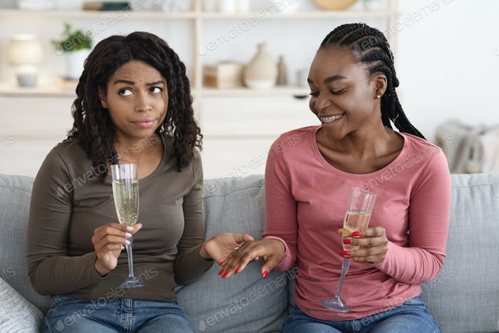 Emotional african woman showing her friend ring