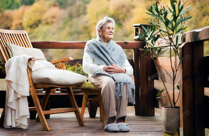 An elderly woman sitting outdoors on a terrace on a sunny day in autumn.