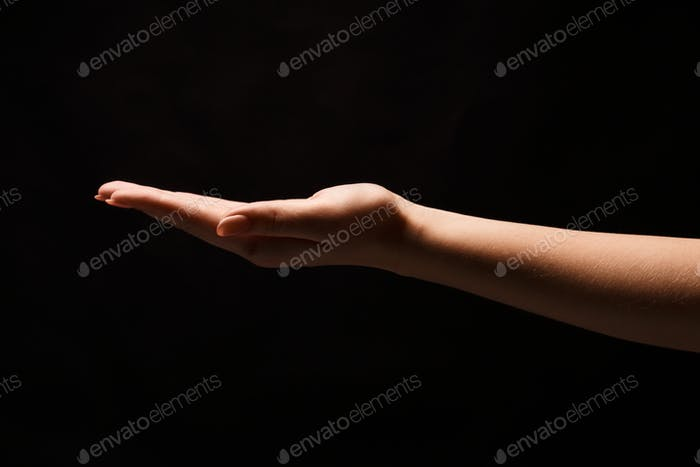 Woman holding palm open isolated on black