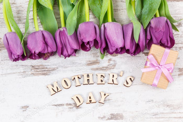 Bouquet of purple tulips and gifts for mother's day on white rustic boards