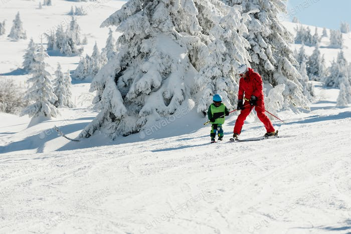Ski instructor and little boy on mountain