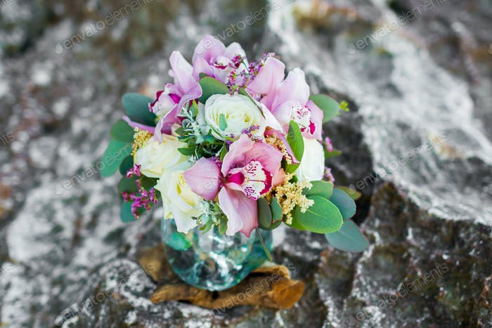 Tender bridal bouquet with pink orchids and white roses in glass pot. Wedding arrangement