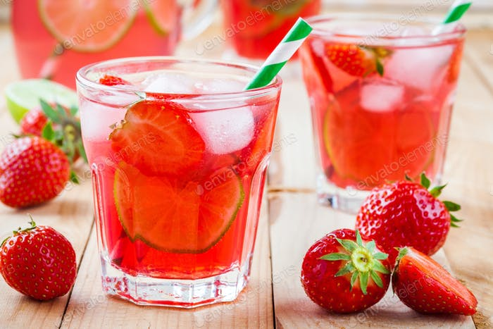 Strawberry lemonade with lime and ice in a glass